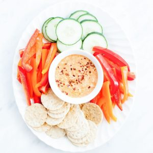 Harissa feta dip on a white platter with sliced vegetables.