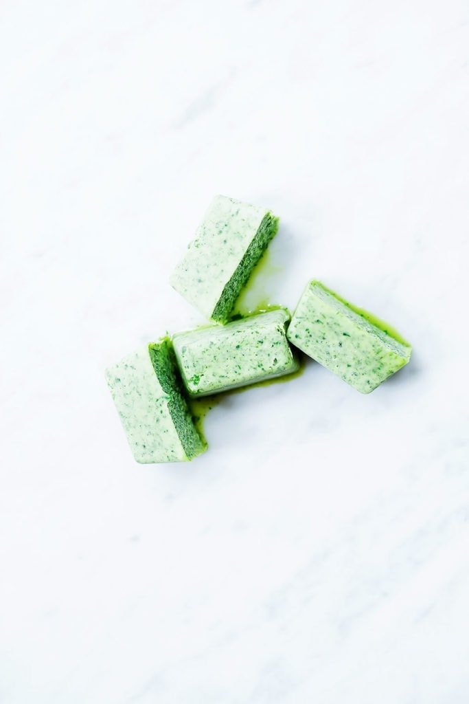 Herbs blended with oil and frozen into cubes on white background.