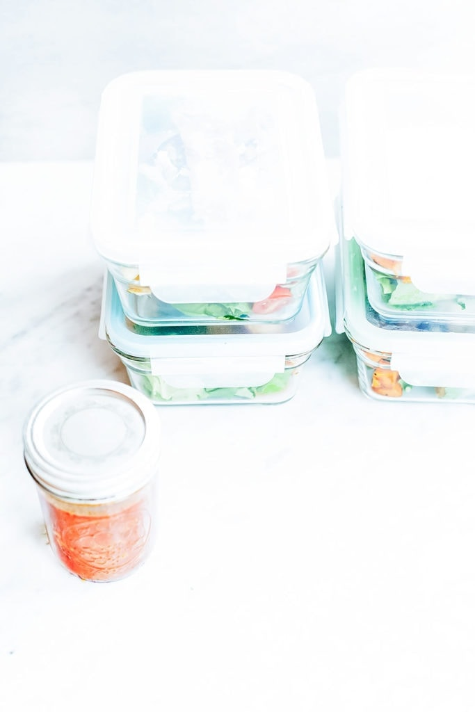 Meal prep containers with harissa dressing in a jar.