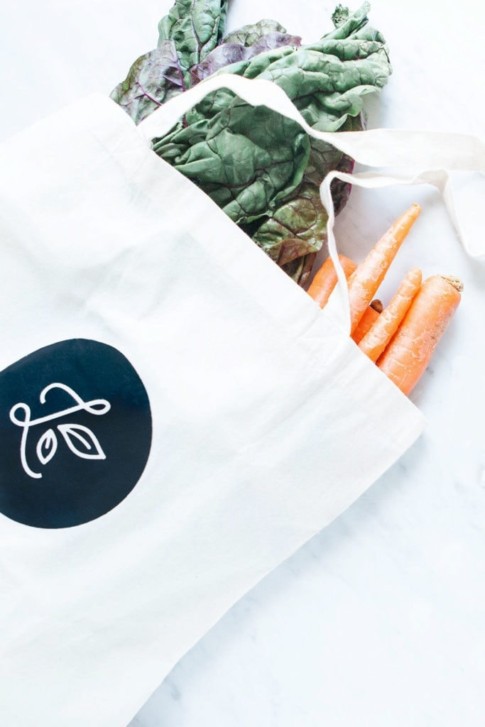 Loveleaf Co. tote bag with carrots and collard greens.