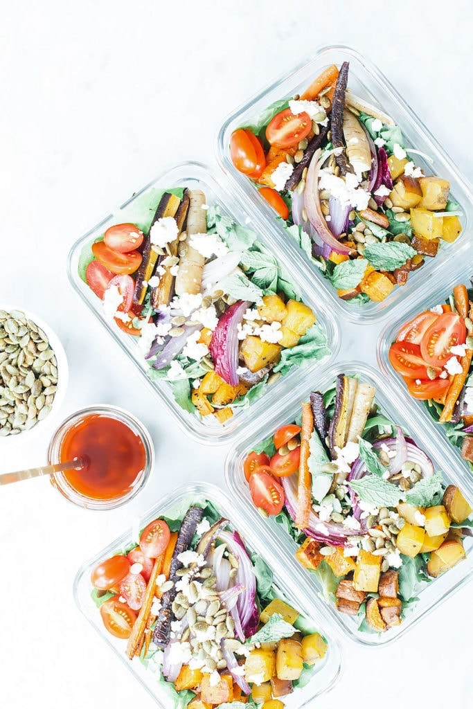 Rainbow harissa salads in five meal prep containers with a jar of harissa dressing.
