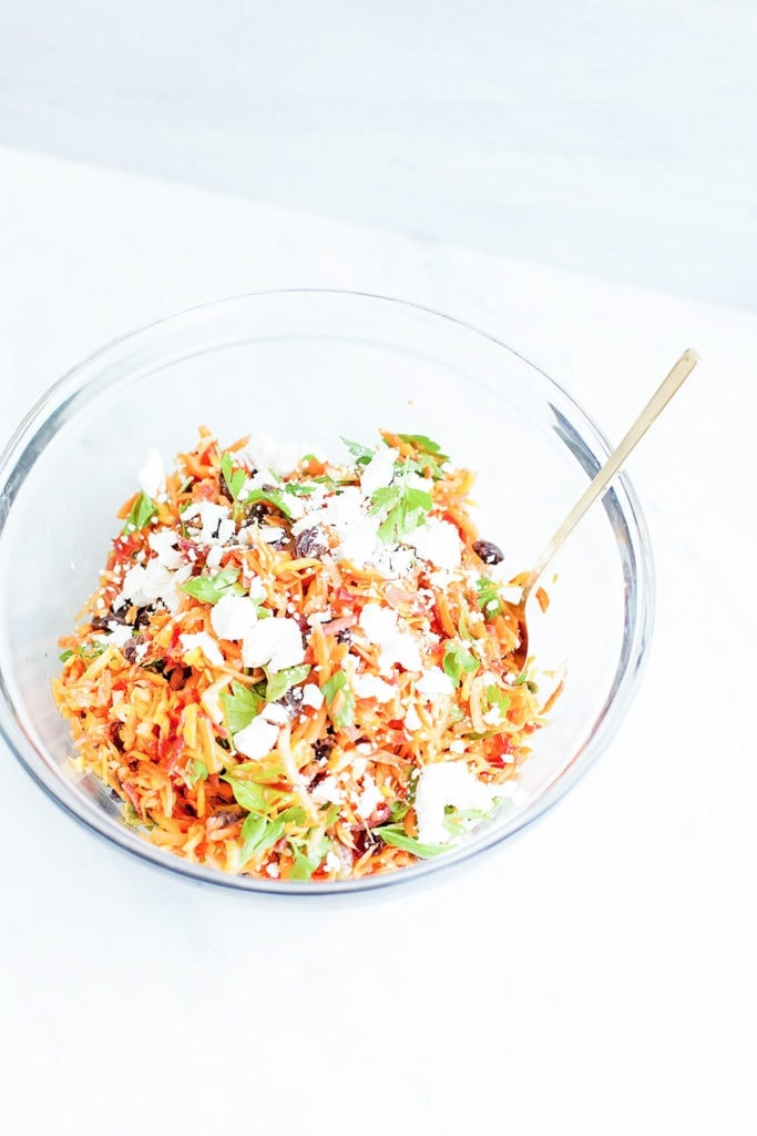 Moroccan harissa chicken salad in a glass bowl on white background.