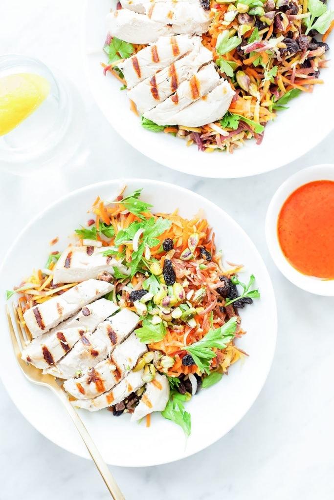 Moroccan harissa chicken salad in white bowls on white background.