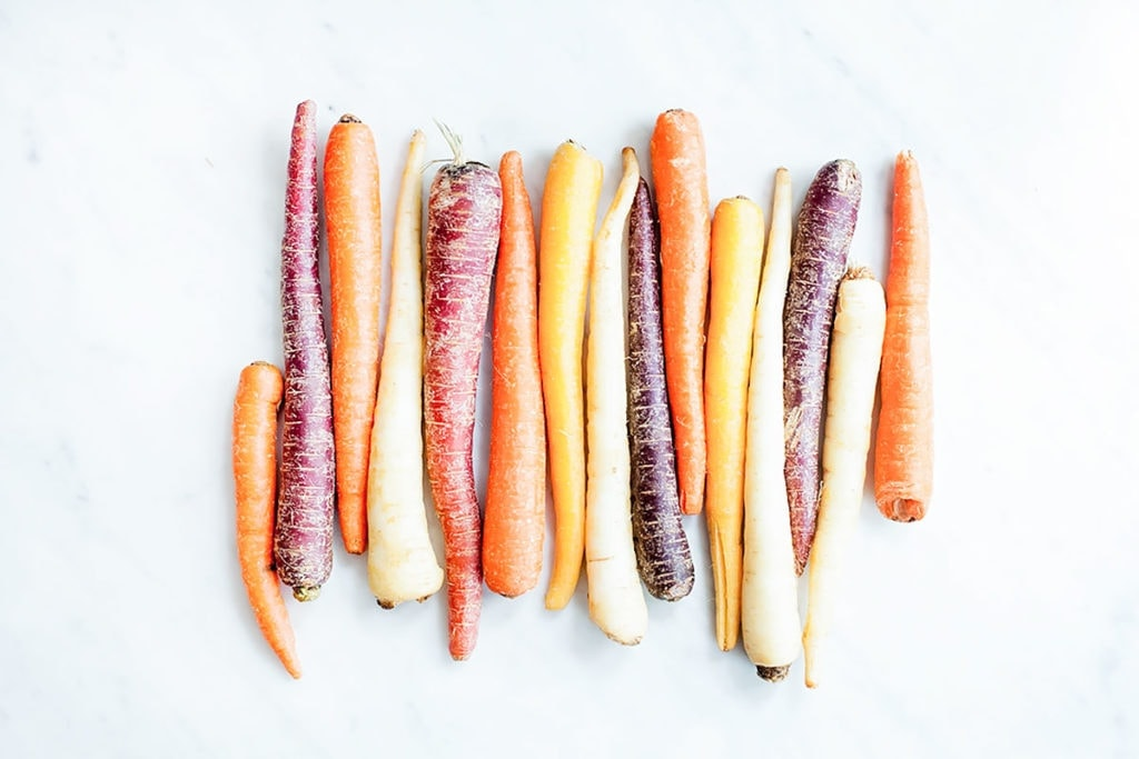 Rainbow carrots lined up on a white marble surface.