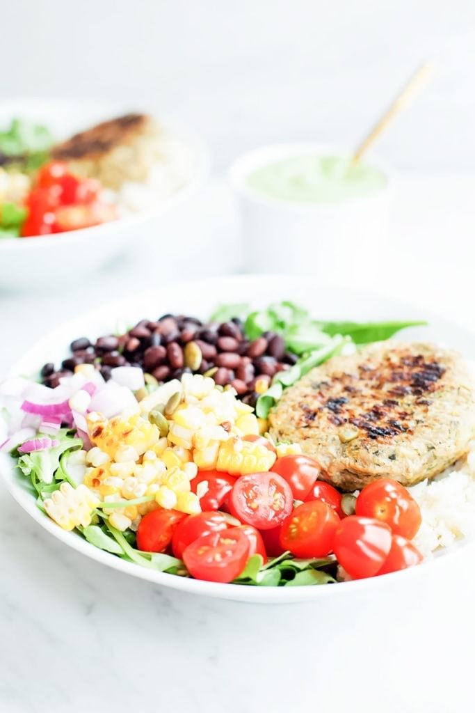 Southwestern burger bowls in white bowls on white background with bowl of green avocado dressing.