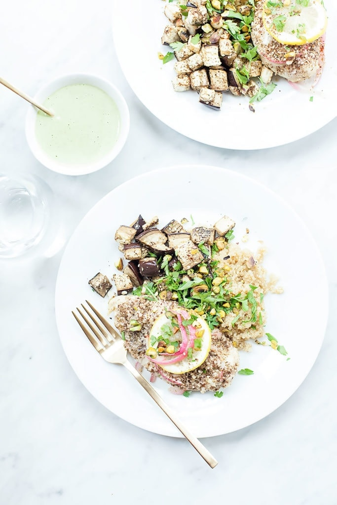 Za'atar roasted chicken and eggplant bowls on a white plate with a jar of green tahini sauce on the side.