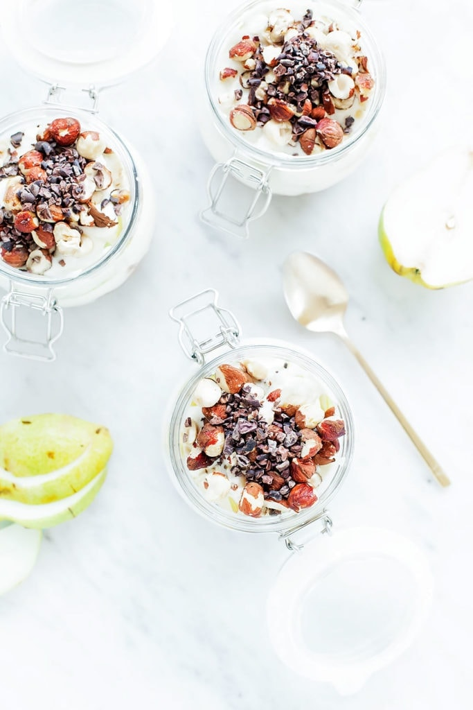 Chocolate, hazelnut, and pear overnight oats layered in three jars photographed from above.