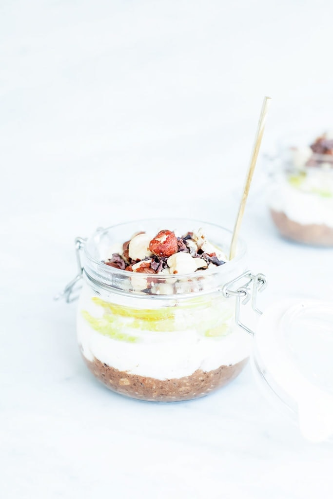 Chocolate, hazelnut, and pear overnight oats layered in a jar photographed from the side.