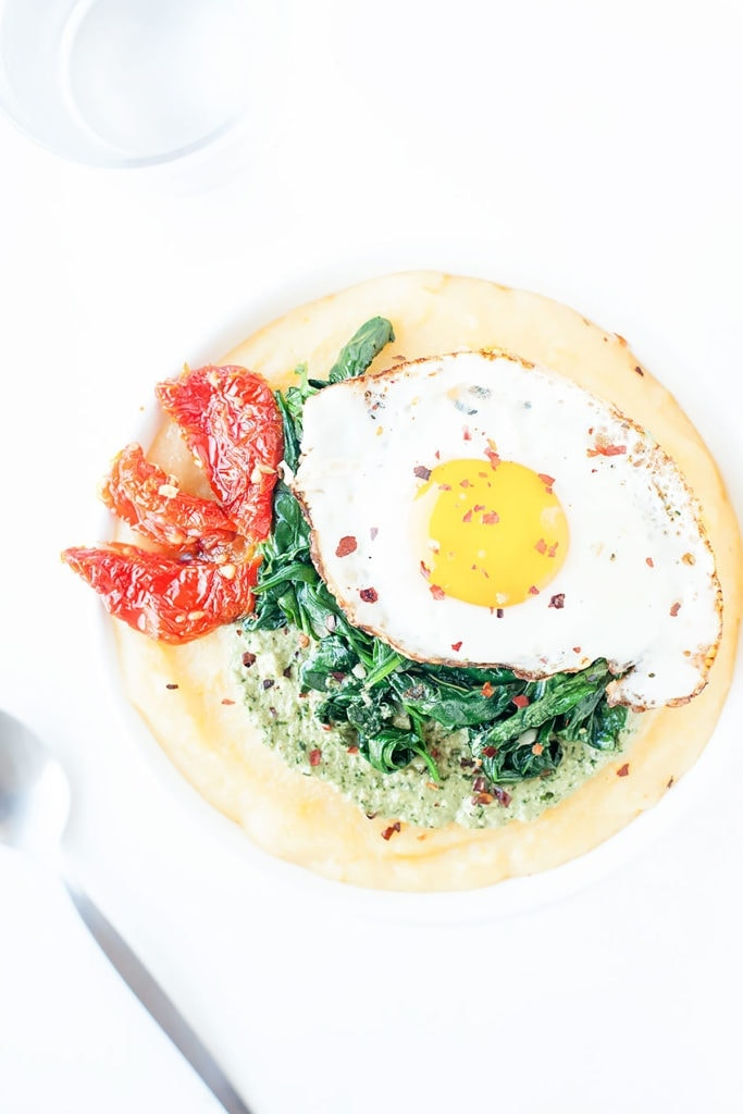 Pesto polenta bowls with eggs, spinach, and sun-dried tomato in a white bowl with a white background.