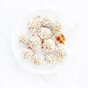 Pumpkin spice energy bites with one with a bite taken out on a white plate.