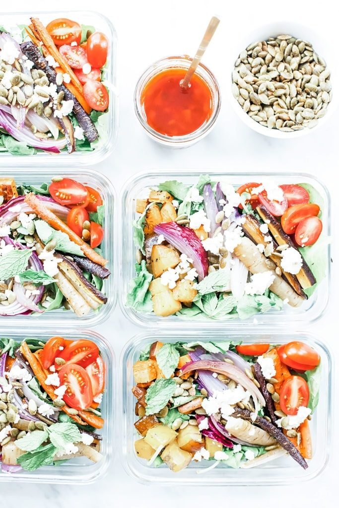 Rainbow harissa bowls in five meal prep containers with harissa dressing and pumpkin seeds.