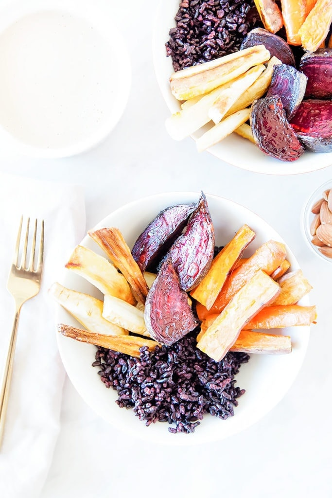 Root vegetables and black rice in two white bowls on a white background.