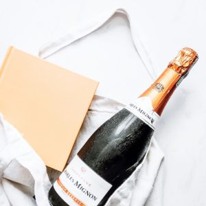 A bottle of champagne in a white bag.