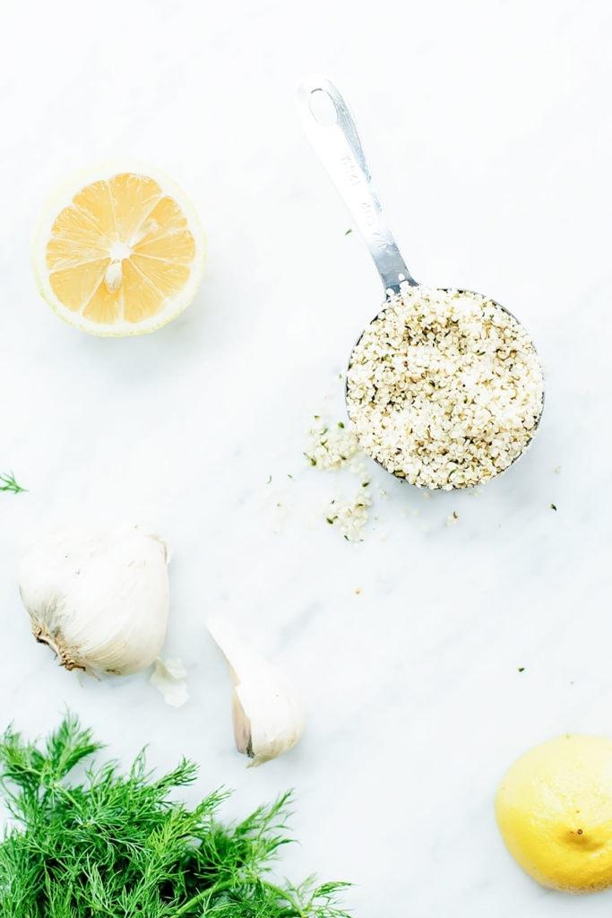 Vegan hemp seed dressing ingredients on a white surface.