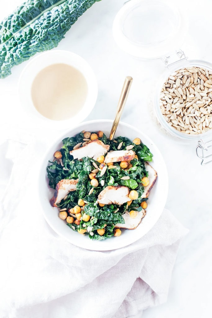 Kale tahini Caesar salad with chicken and crispy chickpeas in a white bowl.