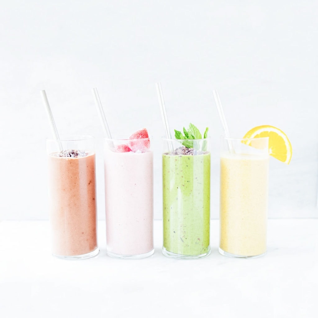 Four colorful smoothies in glasses with straws.