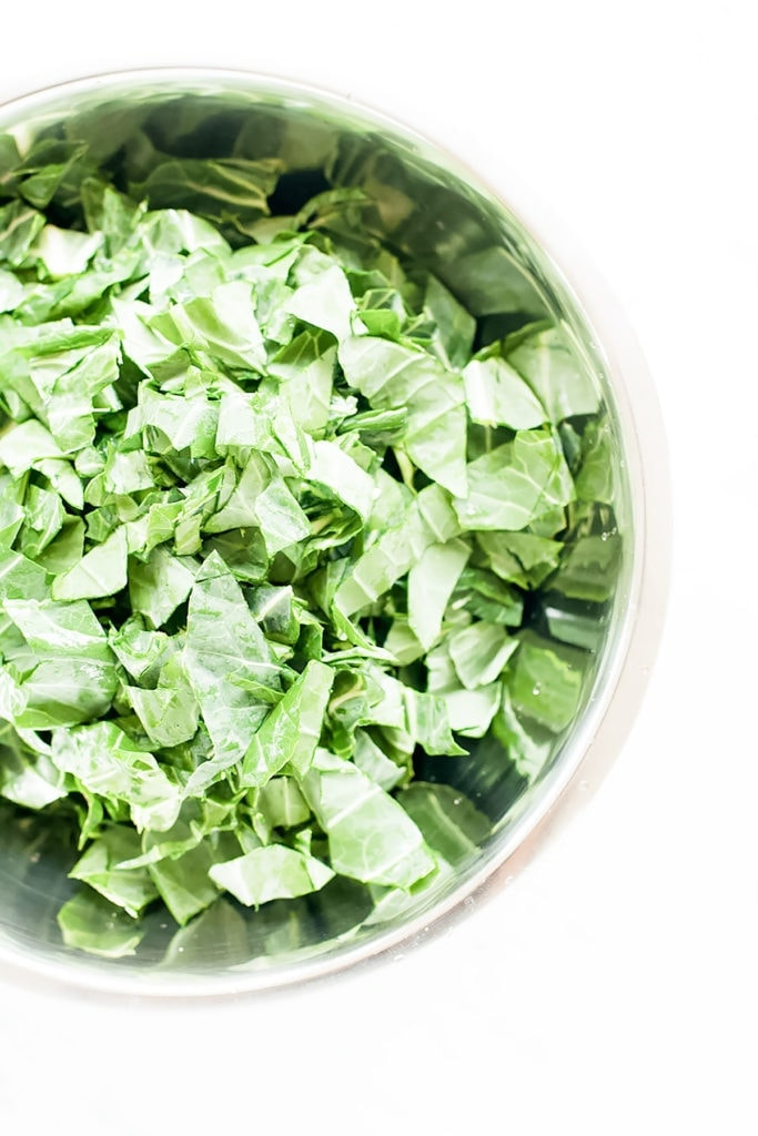 Fresh chopped collard greens in a metal bowl.