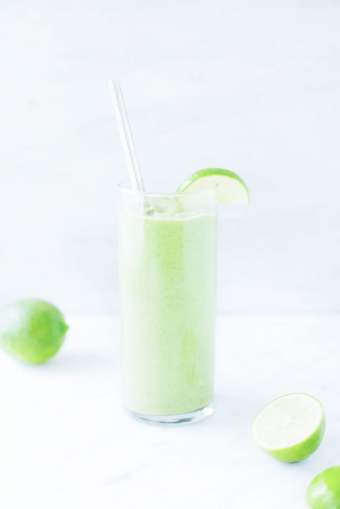 Green lime ginger smoothie in a tall glass with a straw and lime slice.