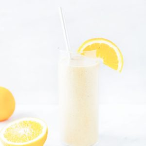Orange creamsicle smoothie in a tall glass with a straw and metal straw.