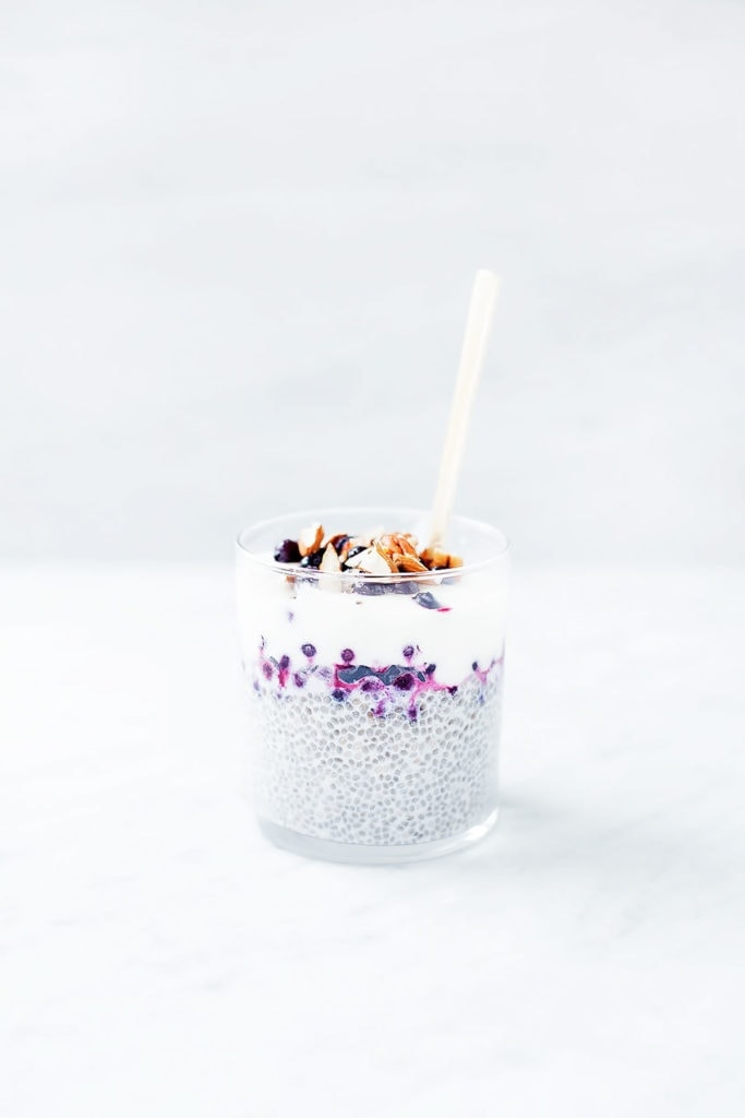 Blueberry pie chia puddings layered with yogurt and blueberries in a glass.