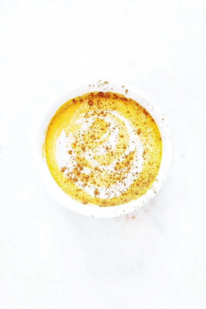 Pumpkin spice latte in coconut milk and cinnamon in a white mug.
