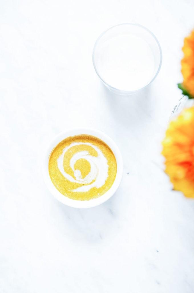 Pumpkin spice latte in coconut milk in a white mug.