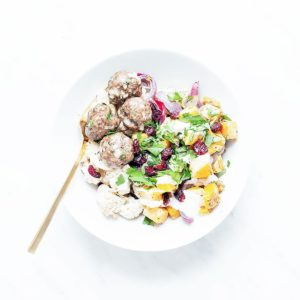 Butternut squash bowls with baked meatballs and tahini sauce in a white bowl.