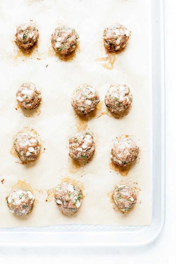 Baked meatballs on a baking sheet.