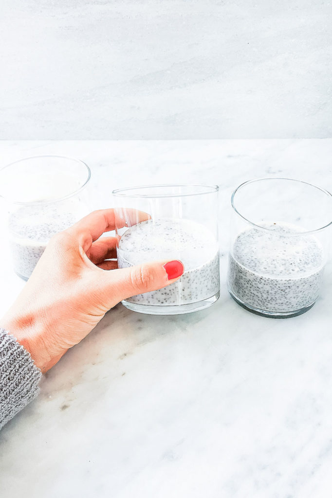 Three glass jars with chia seed pudding and a hand holding one.