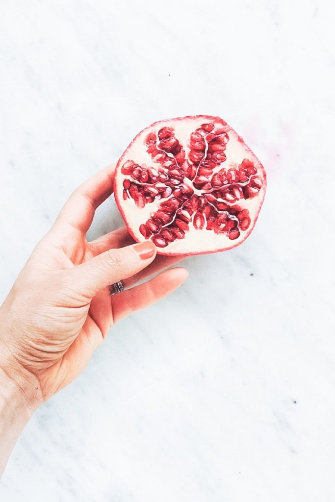Pomegranate cut in half being held by a hand on white surface.