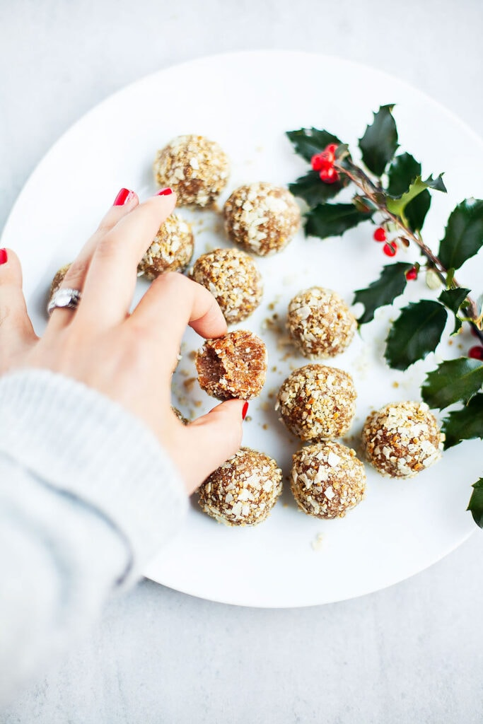 Gingerbread energy bites on a white plate with hand picking one up.