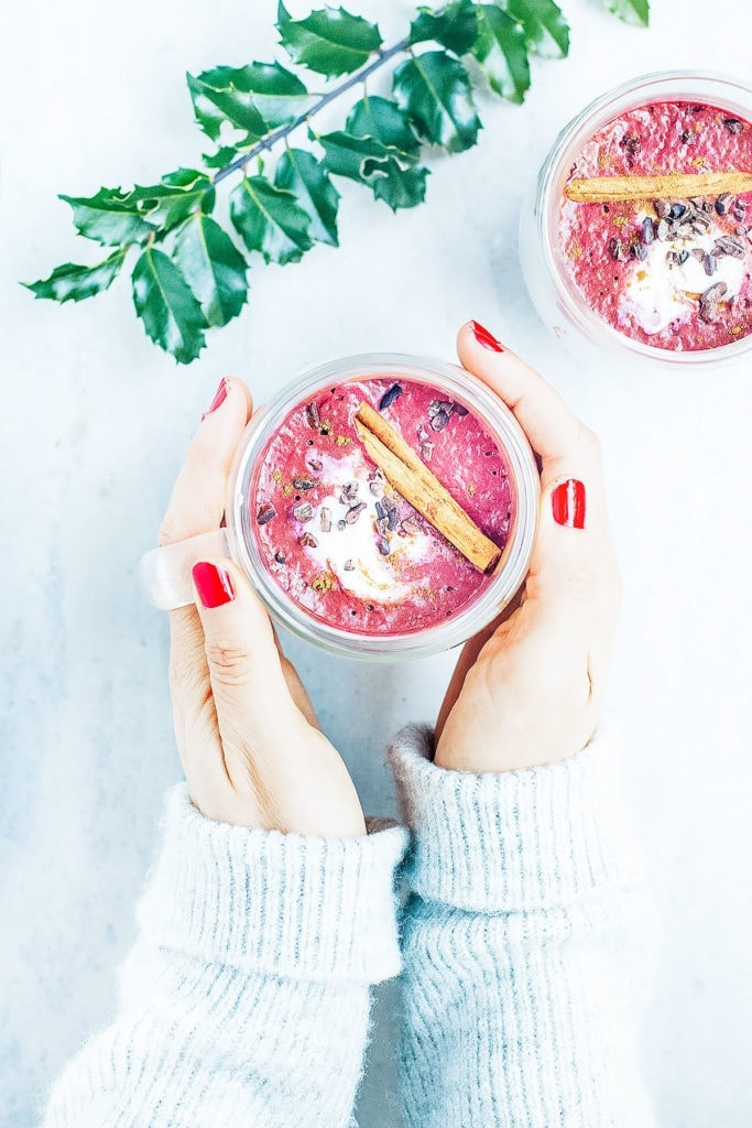 Red velvet beetroot hot chocolate in a glass mug with hands holding it.