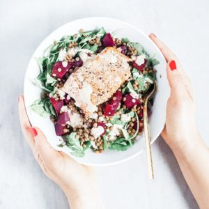 Beet and salmon salad in white bowl being held.