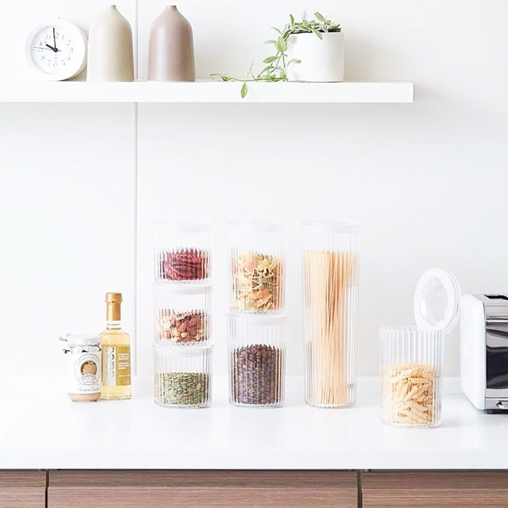 Bulk bin items in jars on a white kitchen counter.