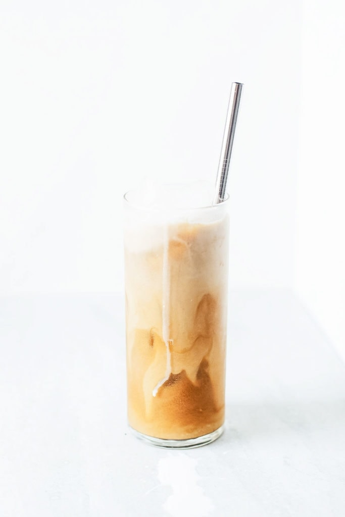 Coconut cold brew coffee with coconut milk in a tall glass with ice and a straw.