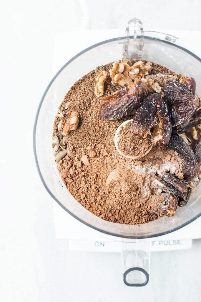 Vegan seed cycling brownie bite ingredients in a food processor.