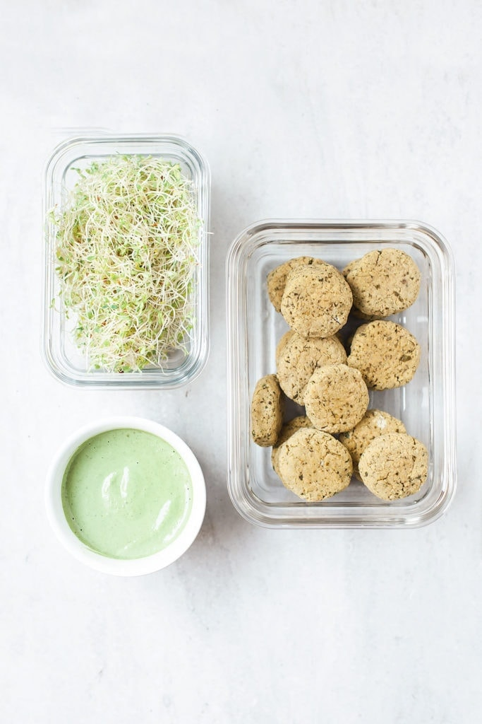 Baked falafel, green tahini sauce, and sprouts in separate meal prep containers.