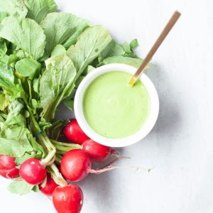 Green tahini sauce with a bunch of radishes.