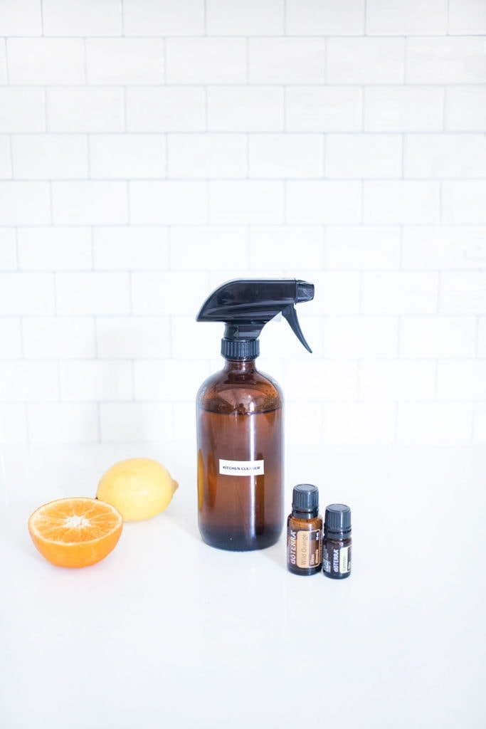 A spray bottle of non-toxic kitchen cleaner with essential oils, an orange, and a lemon.