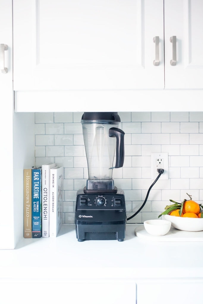 Vitamix, cookbooks, and a bowl of oranges on a white kitchen counter.