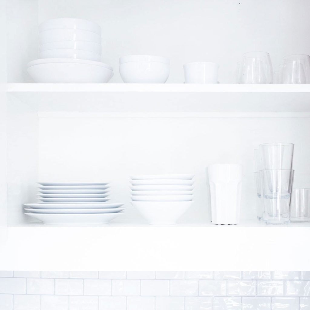 A while kitchen with an open cabinet full of white plates and bowls.