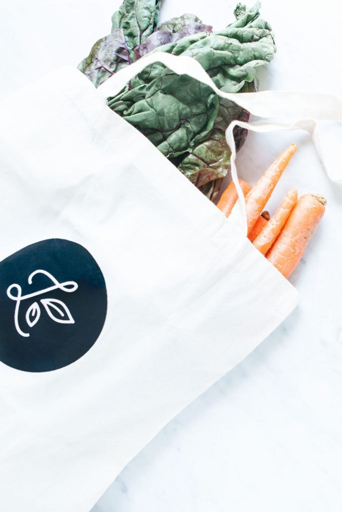 Loveleaf Co. tote bag filled with greens and carrots.