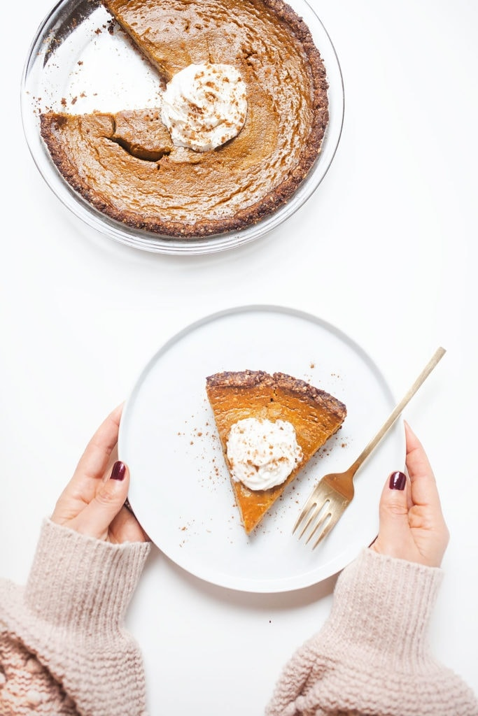 Gluten-free, dairy-free pumpkin pie on being held with a dollop of coconut whipped cream.
