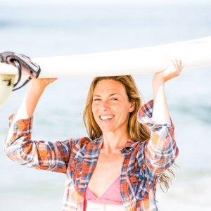 Emily Tyson holding a surfboard at the beach.