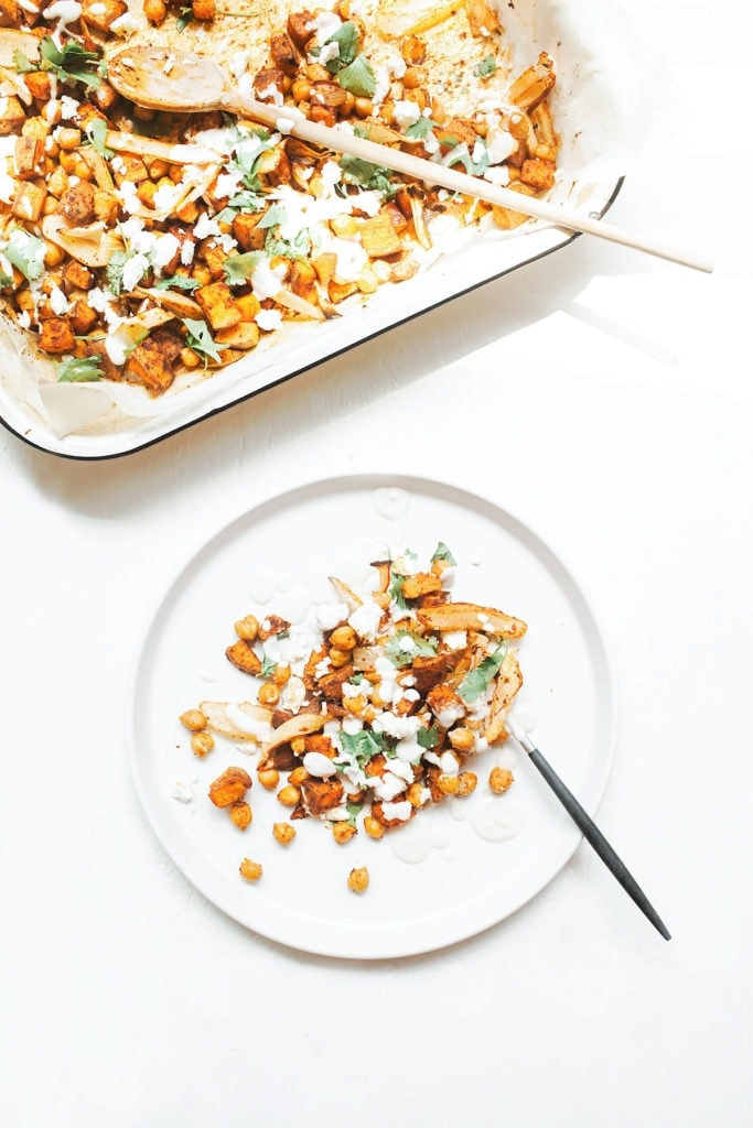Sheet pan harissa chicken with sweet potatoes on a white plate.