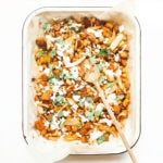 Sheet pan harissa chicken with sweet potatoes in a white casserole dish.
