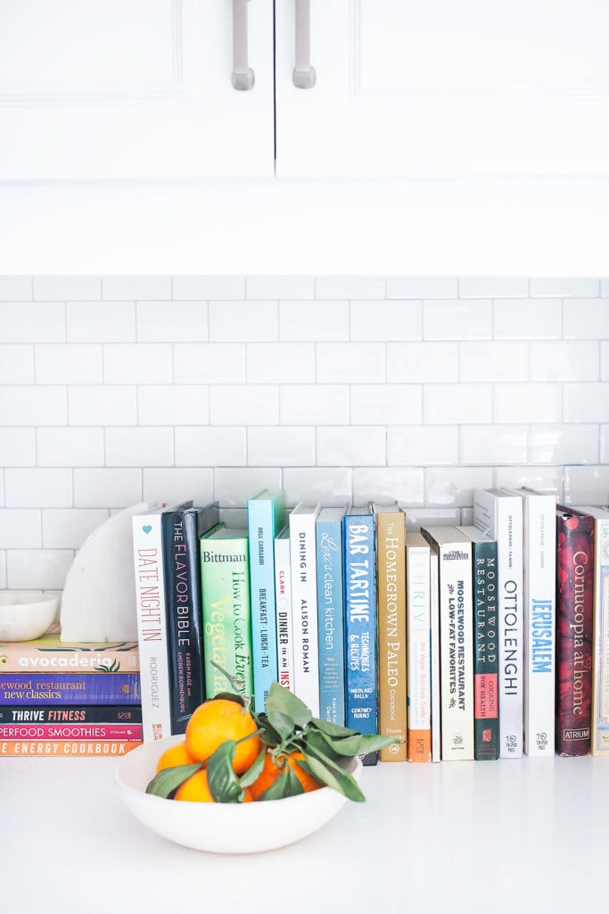 Cookbooks and a bowl full of oranges in front of white subway tile.