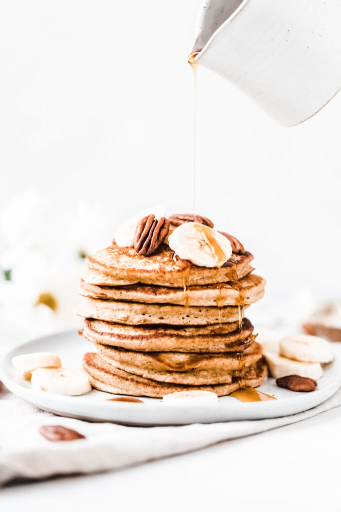 Stack of banana oat pancakes on a white plate being drizzled with maple syrup.