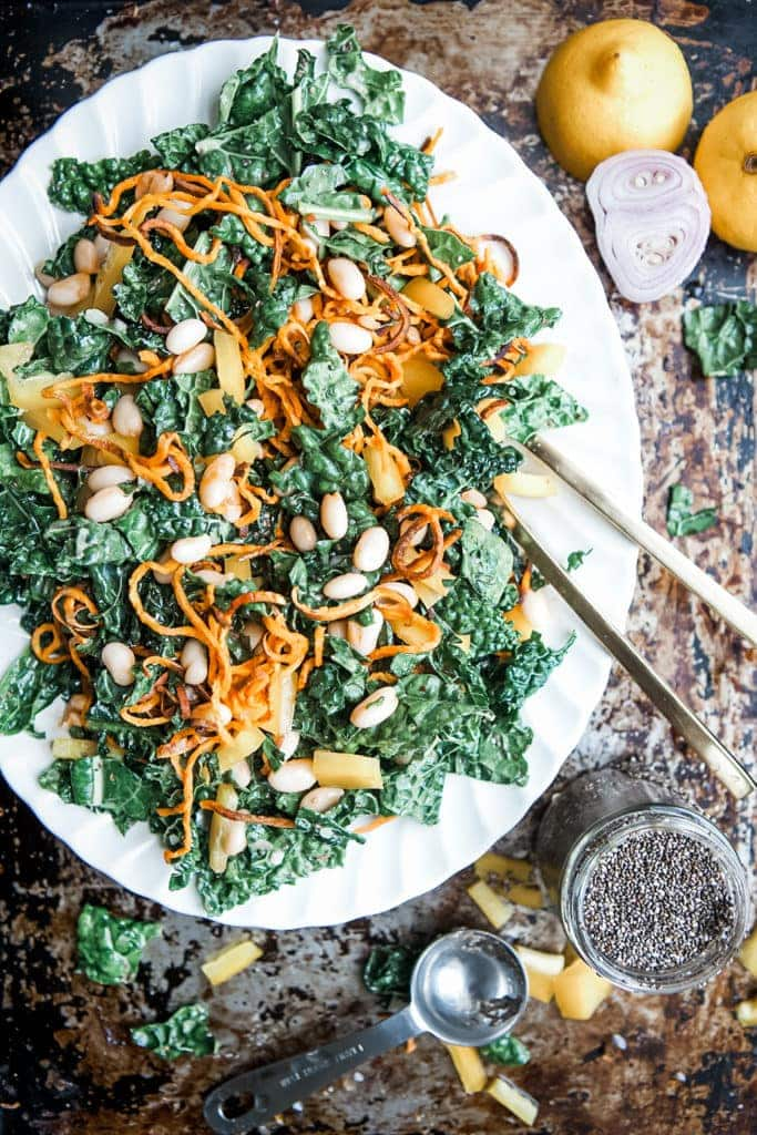 Kale and cannellini bean salad with lemon chia seed dressing on a white platter.