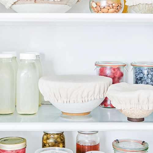 Linen bowl covers on bowls in a fridge.